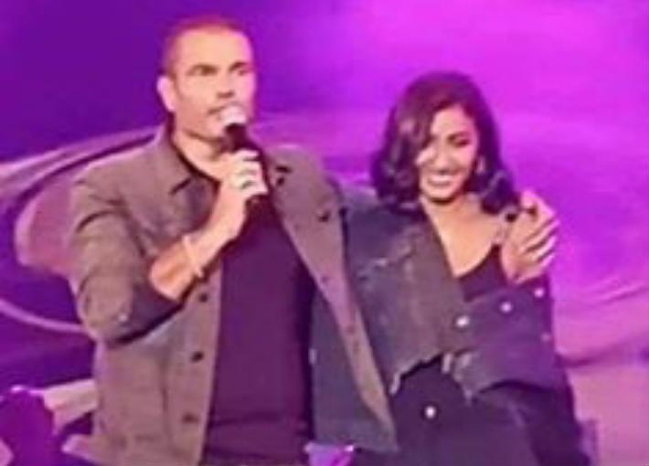 بالفيديو- عمرو دياب ودينا الشربيني يتبادلان القبلات على المسرح