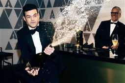 بالفيديو- رامي مالك يرش الجميع بالشامبانيا الفاخرة عقب فوزه بالأوسكار