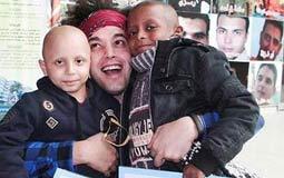جريني يحتضن طفلين من محبيه وهما يحملان أوراق تاريخهما الصحي57357